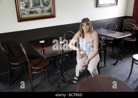 A woman sitting in a very old fashioned pub at the Black Country Museum, near Dudley, West Midlands UK - Stock Photo
