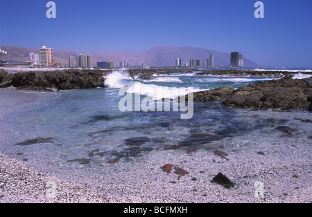 View along coast to modern skyscrapers in distance, Iquique , Chile - Stock Photo