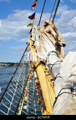 Bowsprit on sailing tall ship with furled sails rope shroud and flags - Stock Photo