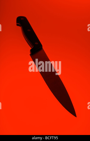 Kitchen knife on red background - Stock Photo