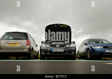 Broken down car in an airport car park - Stock Photo