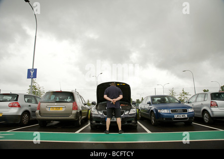 Broken down car in an airport car park with owner - Stock Photo