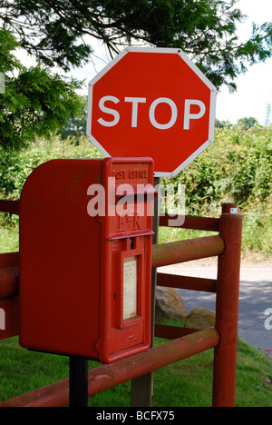 Rural post box by a road stop sign - Stock Photo
