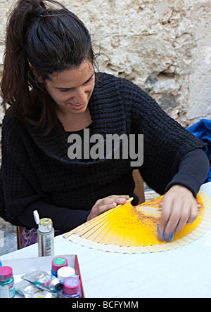 Woman making hand painted fans for tourist souvenirs in market Sineu Mallorca Spain - Stock Photo