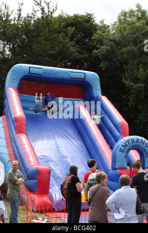 Children on an inflatable slide at an English village show. Ambergate, Derbyshire, England, U.K. - Stock Photo
