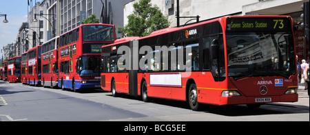 Long queue of buses in Oxford Street London with advertising panel digitally blanked out - Stock Photo