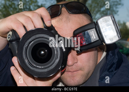 Close up of a man using a canon digital slr camera and flash - Stock Photo