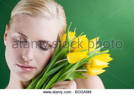 A young woman holding a bunch of yellow tulips, eyes closed - Stock Photo