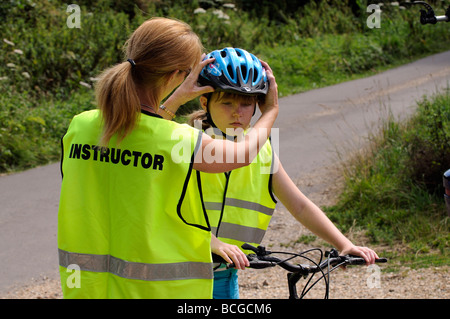 Female cycle training instructor wearing a high visibility reflective safety jacket adjusts a pupils cycle helmet - Stock Photo