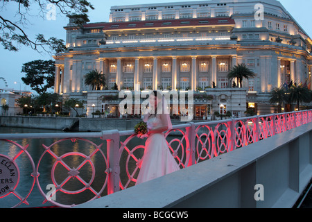 A newly married bride poses on the Anderson bridge in front of the Fullerton hotel at dusk - Stock Photo