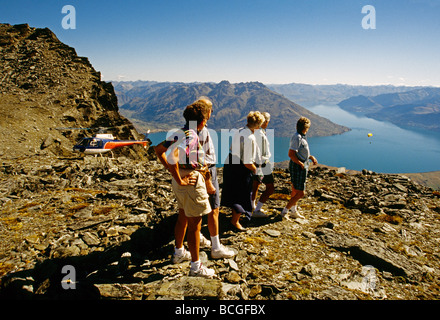 Tourists watch paraglider over Lake Wakatipu's Queenstown Bay from top of Remarkables mountains after helicopter - Stock Photo
