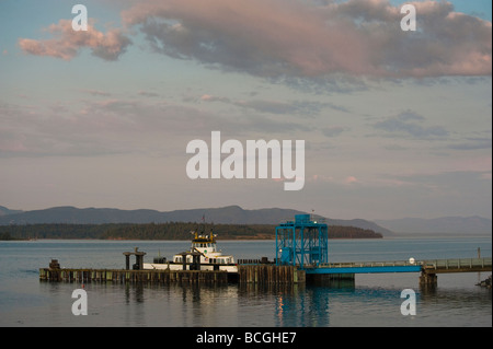 As the sun sets on the Pacific Northwest, the small 20 car Lummi Island Ferry loads passengers for the trip to the - Stock Photo