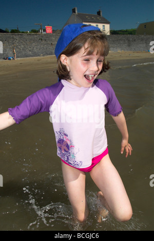 Girl Running Into The Sea at Pendine Beach South Wales UK - Stock Photo