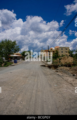 A long straight road with a large dug out hole by the side of the road leading into a town near La Torre Dominican - Stock Photo