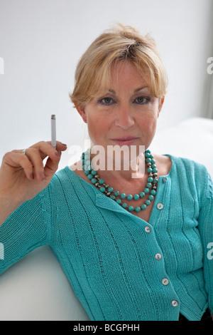 Senior woman is smoking a cigarette - Stock Photo