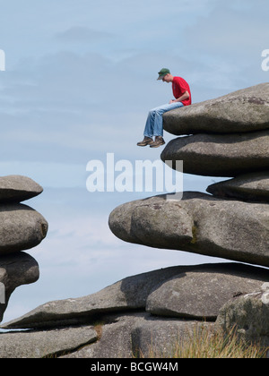 Teenager sat on rocks on the edge of the Cheesewring Quarry Bodmin Moor Cornwall - Stock Photo