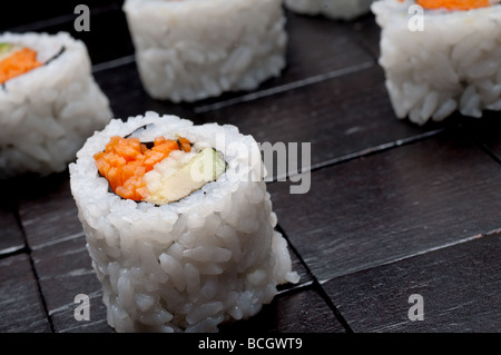 a tilted horizontal shallow focus macro of sushi on a black wooden background - Stock Photo