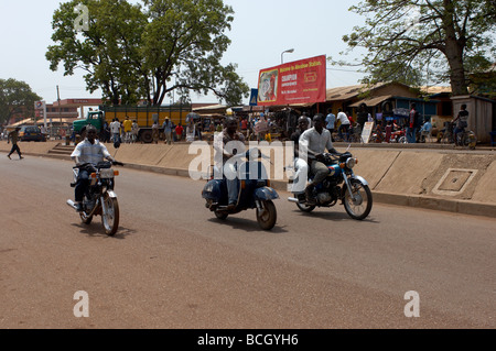 Two motorbikes and a scooter on street in Ghana - Stock Photo