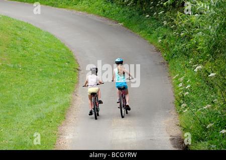 Children cycling along a country lane England UK - Stock Photo
