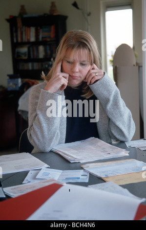 Woman looking at bills in chaos on table - Stock Photo