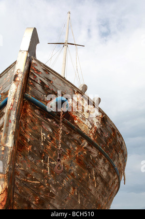 The paint stripped remains of a large wooden ship rot against a cloudy sky - Stock Photo