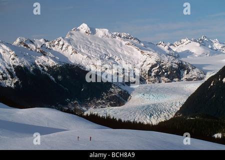 Mendenhall Glacier Southeast Alaska Winter Cross Country Skiers Snow Mountains Forest Sky - Stock Photo