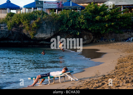 The beach by Sosua in the Dominican Republic showing a man on sun lounger watching a young black boy somersault - Stock Photo
