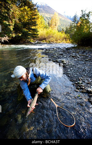 Woman releases a rainbow trout caught while fly fishing on Ptarmigan Creek in the Kenai Peninsula, Alaska during - Stock Photo