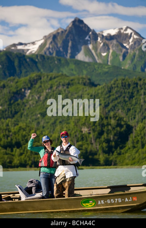 Fisherman holding caught Silver Salmon while standing in a boat on Big River Lakes in Southcentral Alaska during - Stock Photo