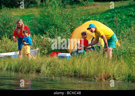 Family tent camping and fishing along lake shore AK Southcentral Summer Scenic - Stock Photo