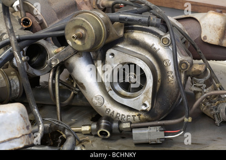 broken turbocharger sitting on a workbench in a car garage - Stock Photo