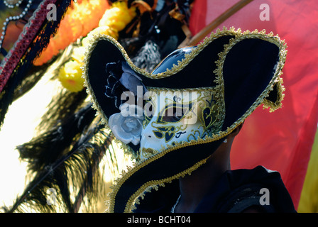 Man in street festival with black gold and white mask - Stock Photo