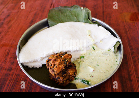 A traditional breakfast is served in an inexpensive restaurant in Mysore, India. Malliga Idly and Vada are served - Stock Photo