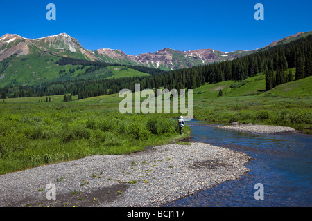 Fly fisherman on the East River and the Elk Mountains beyond Colorado USA - Stock Photo