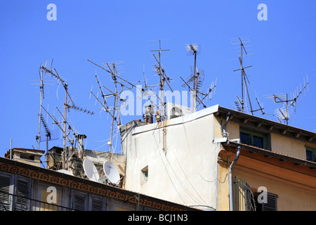 A large number of television aerials and satellite dishes on a rooftop in Nice France - Stock Photo