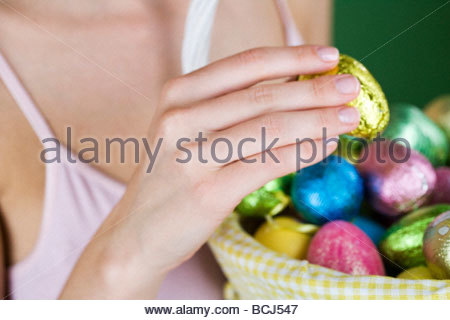 A woman holding a basket of Easter eggs, close-up - Stock Photo