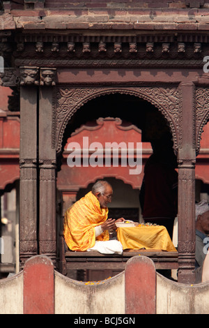 Pashupatinath Temple, Kathmandu, Nepal.  A Sadhu, a Hindu Ascetic or Holy Man, Reading Sacred Texts. - Stock Photo