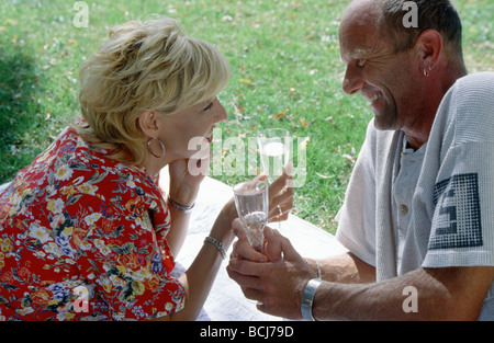 Mature couple champagne together in garden relaxing - Stock Photo