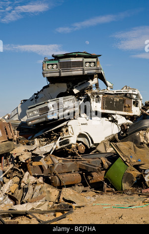 Stack of cars automobiles vehicles in salvage recycling yard against blue sky Barstow California USA - Stock Photo