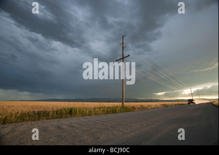 Truck SUV vehicle automobile on unpaved gravel road lined with utility poles at sunset with dramatic sky Montana - Stock Photo