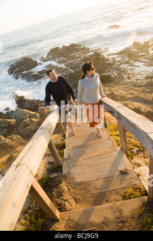Male and female couple walking on wooden steps along cliffs beach in Cambria California with view of ocean - Stock Photo
