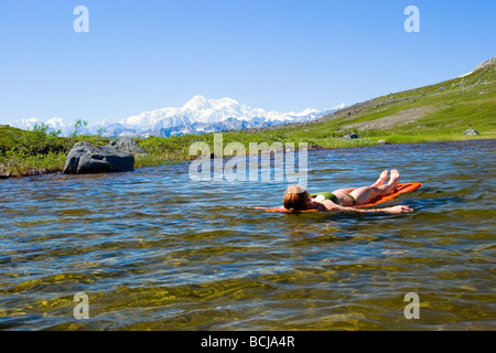 Backpacker takes break and floats on a Thermarest in a remote lake Kesugi Ridge Denali State Park Alaska Southcentral - Stock Photo