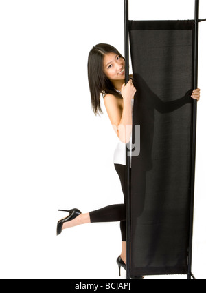 girl smiling from behind folding screen - Stock Photo