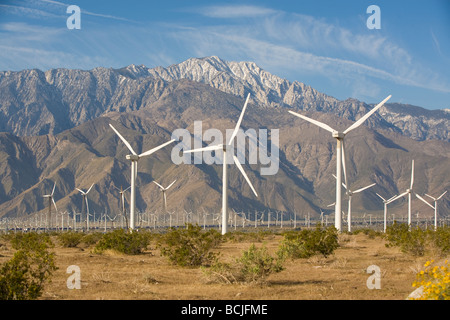Energy generating windmills in desert with snow capped San Jacinto Mountains in background Palm Springs California - Stock Photo