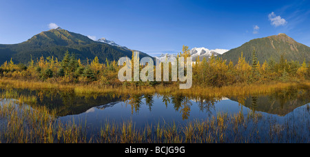 Autumn scene of changing trees reflecting in Mendenhall Lake with Coastal Mountains the background of Southeast - Stock Photo