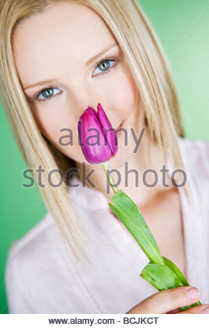 A young blonde woman holding a tulip - Stock Photo