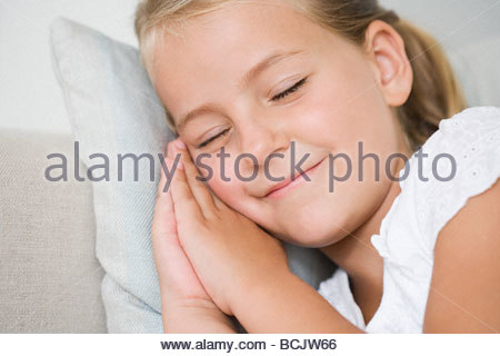 Smiling little girl napping on couch - Stock Photo