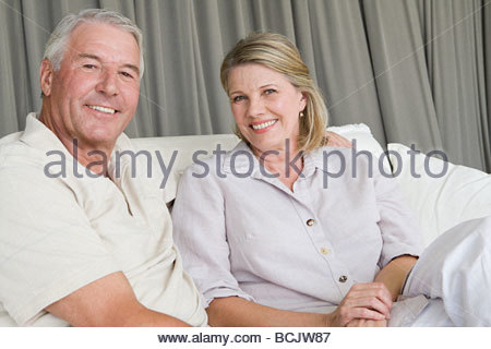 Smiling senior couple sitting on couch - Stock Photo