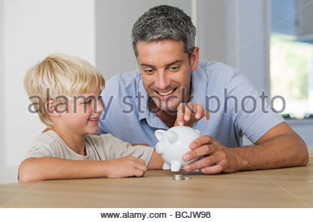 Little boy putting coins in piggybank with his father - Stock Photo