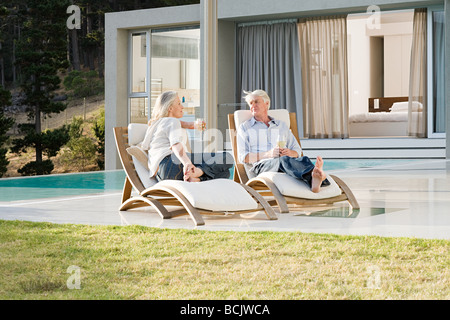 Middle aged couple relaxing on deck chairs by the pool - Stock Photo